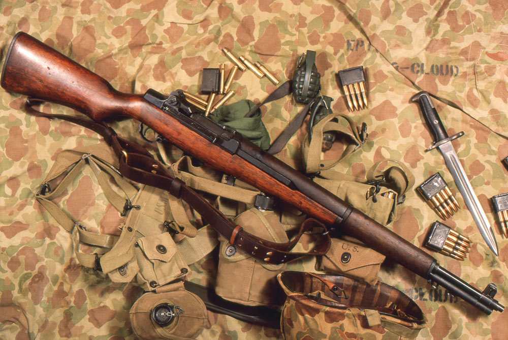 ??) The author's 1943 M1, about 1986, by which time the barrel had been replaced, displayed and photographed here with vintage ammo and U.S.M.C. militaria, on a World War II vintage camouflaged shelter half.