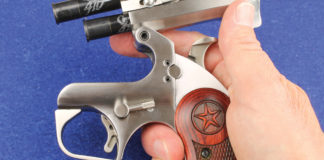 Because of its top hinge, the Bond Arms derringer should be held sideways or slightly inverted to prevent cartridges from sliding out when closing the action. The lever is the barrel release, the auto/manual extractor is mounted on the barrel, and the circular object under the hammer is the cross bolt safety.