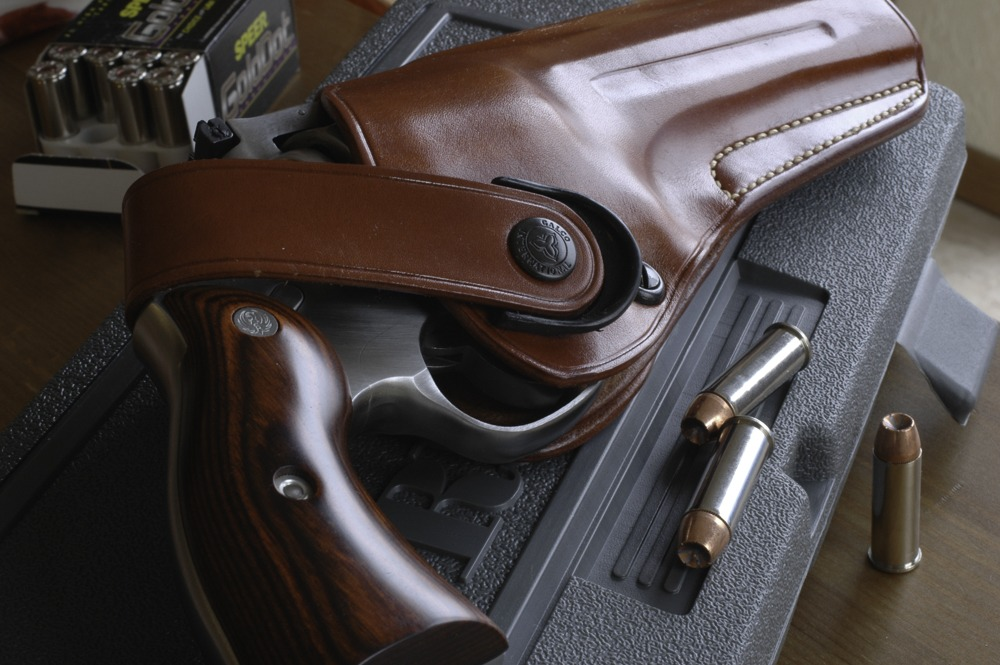 For the Redhawk, author likes the Galco DAO (here) and Phoenix holsters. Note strap tab, tension screw.