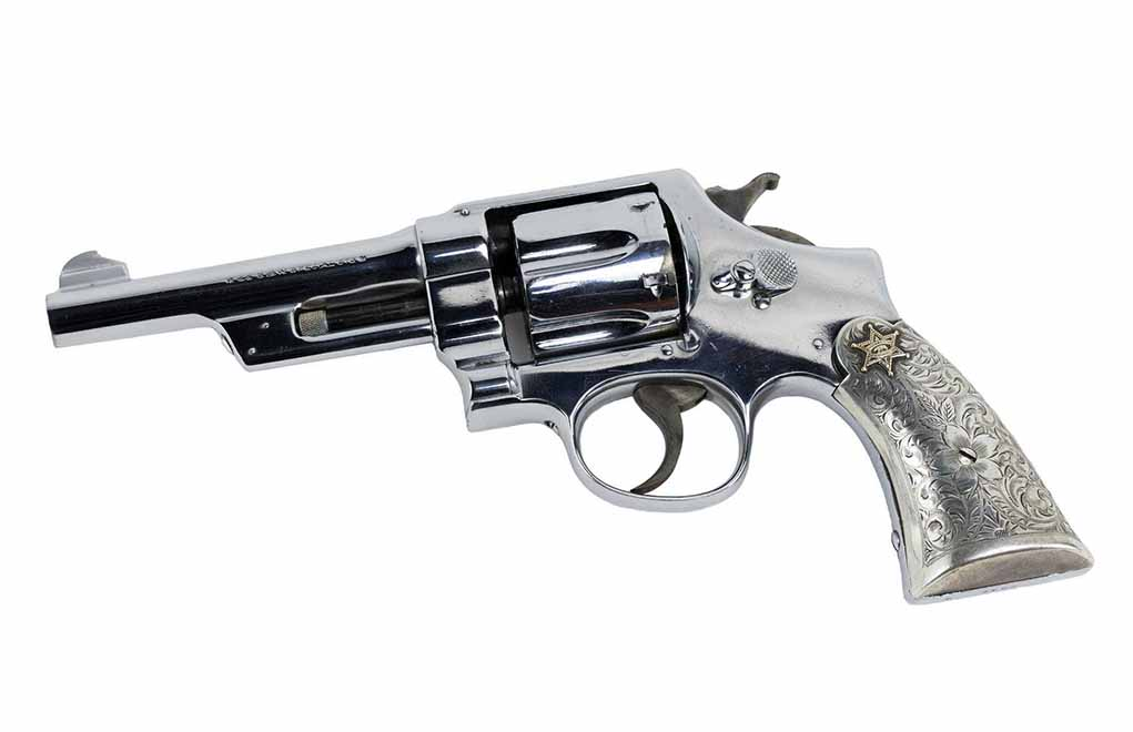 This Hand Ejector First Model belonged to a member of the Los Angeles County Sheriff's Silver Mounted Posse in the 1950s. Its nickel finish was redone at the Smith & Wesson factory. The Bohlin silver grips add a fine touch. (Photo: Guns International)