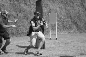 Dan Burwell runs between cover points at IDPA Nationals, Safety Officer with timer running to keep up. Pistol is S&W M&P 9mm.