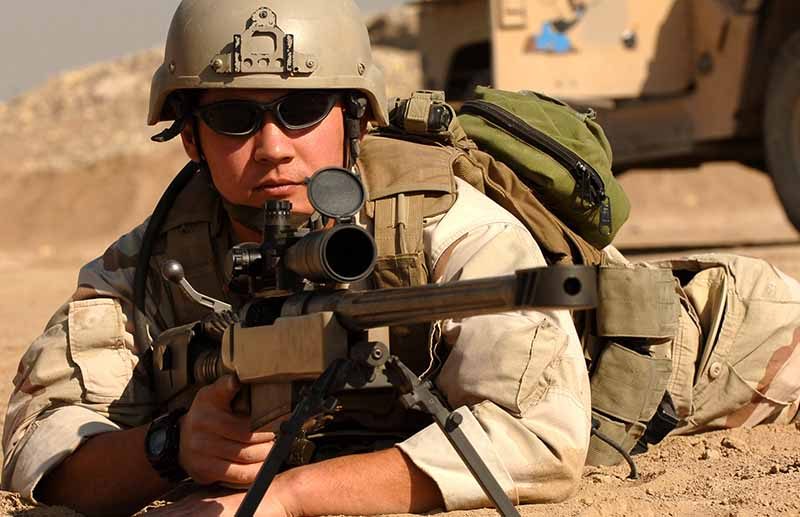 U.S. Navy Boatswain's Mate assigned to Explosive Ordnance Disposal Mobile Unit Eleven (EODMU-11), shoots a McMillan TAC-50 sniper rifle during weapons training at a range in Iraq.
